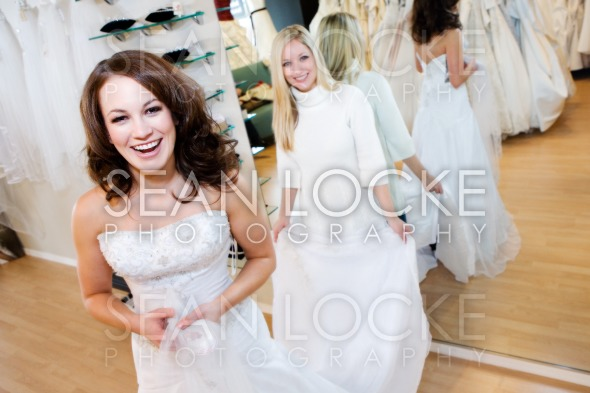 Bride: Woman Trying On Wedding Gown With Help Of Saleswoman Stock Photography Content by Sean Locke