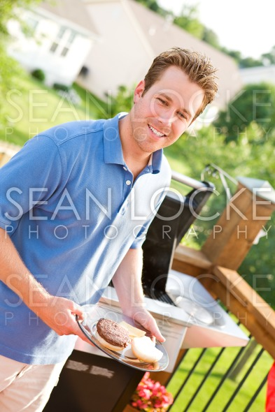 Summer: Dad Serves Up Burgers Stock Photography Content by Sean Locke