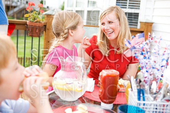 Summer: Mom and Girl Laughing At Table Stock Photography Content by Sean Locke