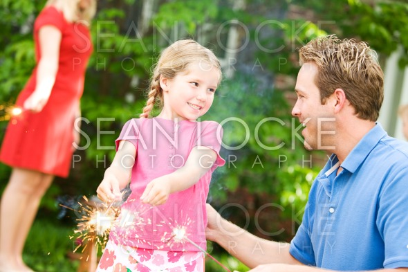 Summer: Dad Teaches Girl To Use Sparklers Stock Photography Content by Sean Locke