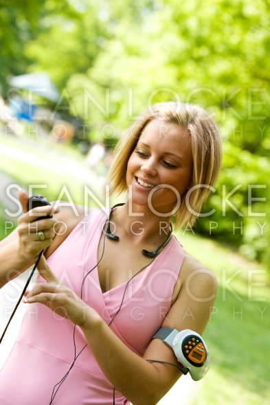 Park: Woman Takes Pulse After Walking Stock Photography Content by Sean Locke
