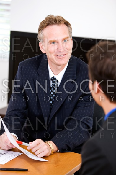 Business: Manager Reviewing Documents With Employee Stock Photography Content by Sean Locke