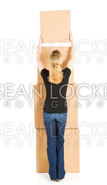 Boxes: Woman Adding Another Box to Stack Stock Photography Content by Sean Locke