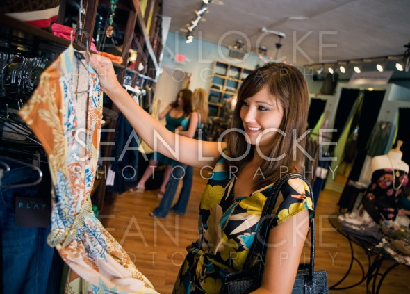 Boutique: Pretty Woman Examines Dress In Store Stock Photography Content by Sean Locke