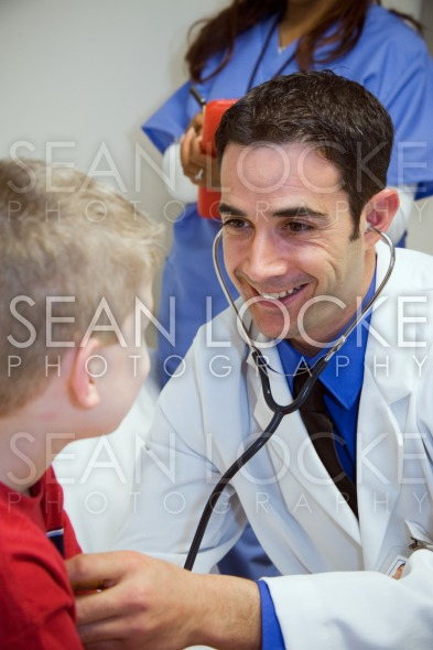 Hospital: Doctor Listens To Boy's Heart In Exam Room Stock Photography Content by Sean Locke