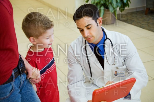 Hospital: Doctor Showing Test Results To Child and Parent Stock Photography Content by Sean Locke