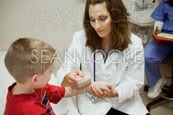 Hospital: Pediatrician Wraps Bandage Around Wrist Stock Photography Content by Sean Locke