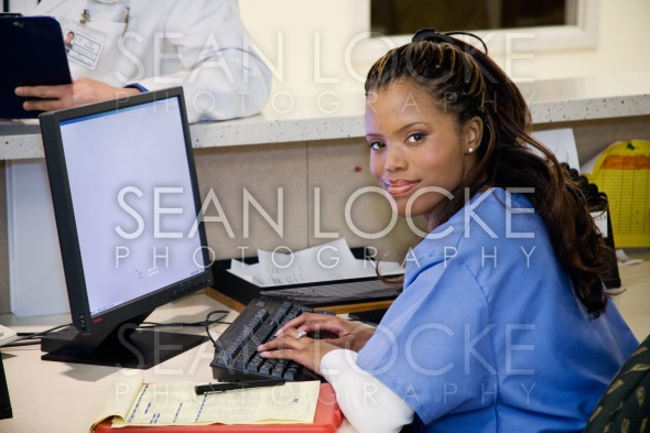 Hospital: Smiling Nurse at Clinic Workstation Stock Photography Content by Sean Locke