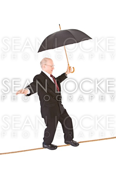 Business: Manager Walking Tightrope with Umbrella Stock Photography Content by Sean Locke